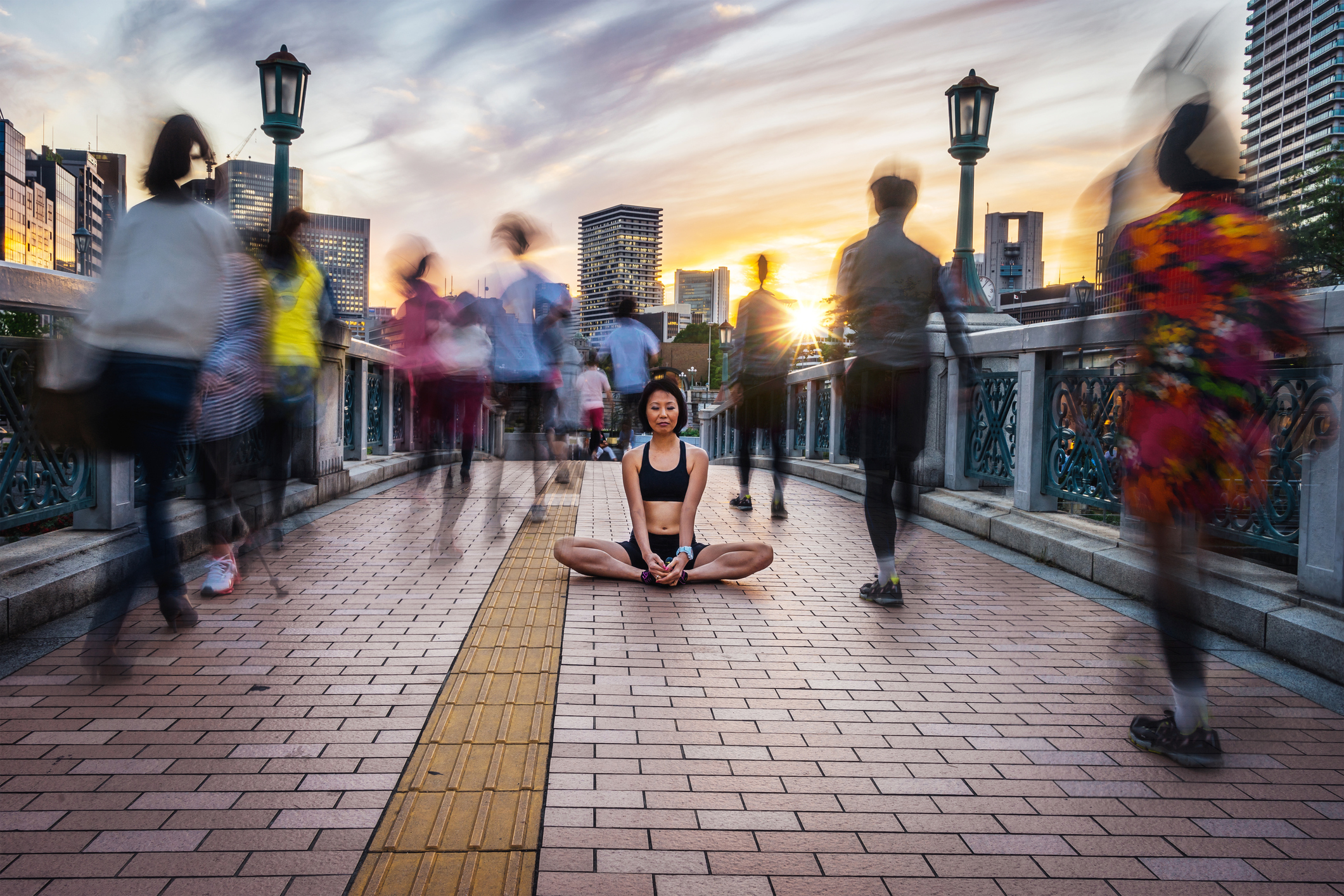 Woman Meditating Into The Crowd At Sunset